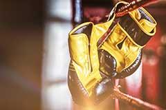 Boxhandschuhe über den Seilen eines Boxrings hängend
